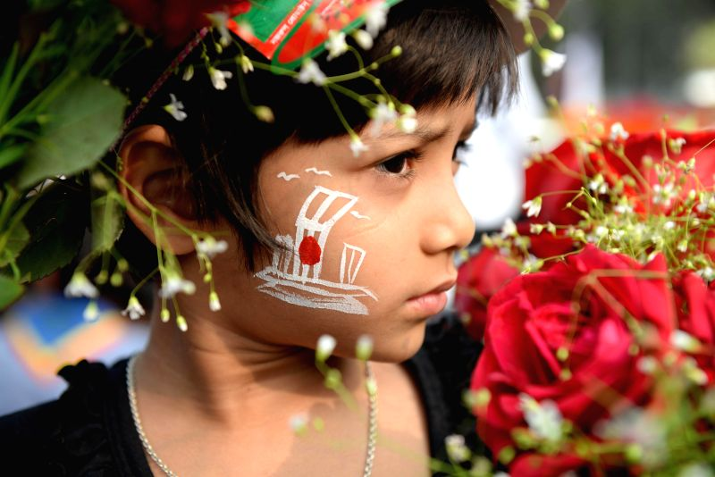 A child holds flowers to mark the International Mother Language Day in front of the Language Martyrs Memorial monument in Dhaka, Bangladesh, Feb. 21, 2015. People pay ...