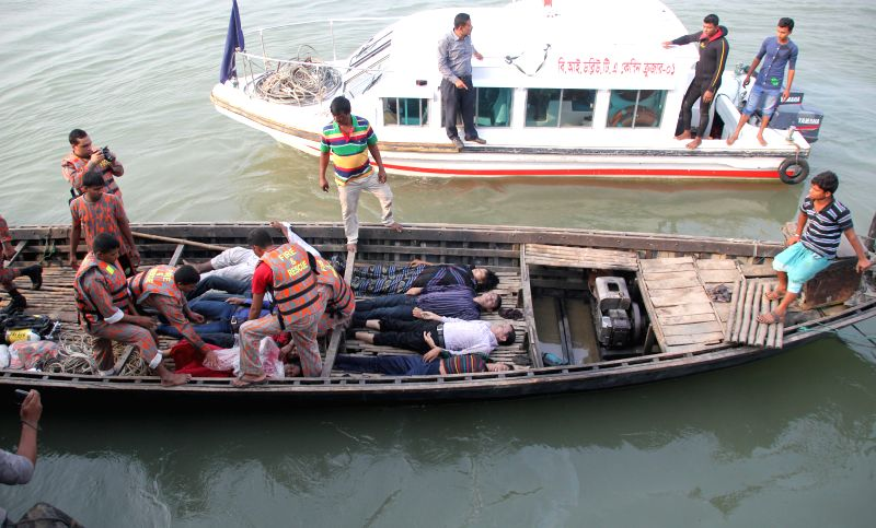Rescuers place bodies of victims on a boat after a ferry accident on the Padma River in Manikganj district, Bangladesh, Feb. 22, 2015. Death toll in Bangladesh's ...