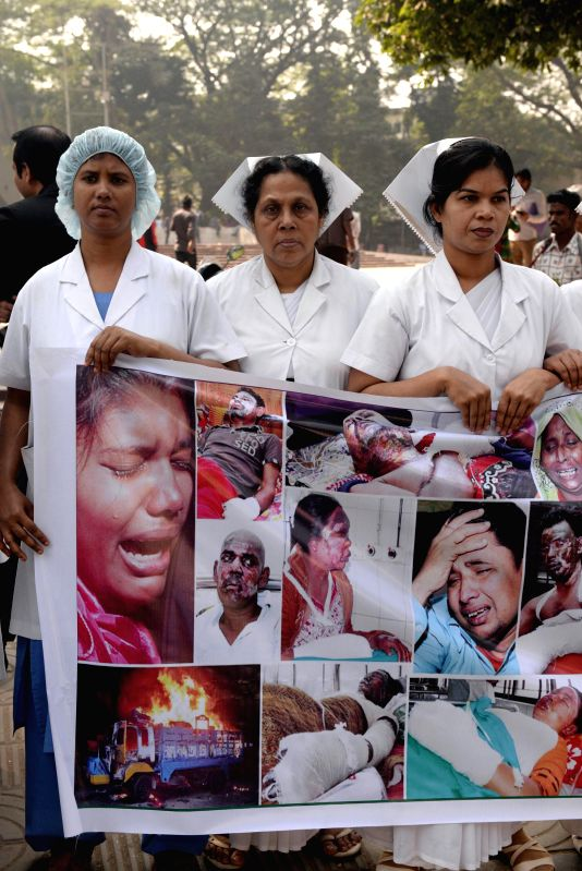 Nurses attend a protest against the ongoing arson attacks during the blockade violence across the country in front of Dhaka Medical College Hospital in Dhaka, ...