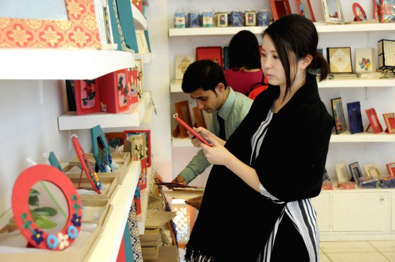 Visitors look at products at a stall during the Dhaka International Trade Fair in Dhaka, Bangladesh, Jan. 4, 2015. The Dhaka International Trade Fair held in Dhaka ...