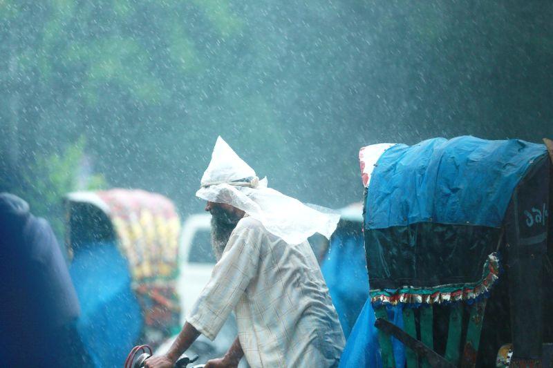 DHAKA, July 18, 2016 - A rickshaw puller carries passengers in the rain in Dhaka, Bangladesh, on July 18, 2016. (Xinhua/Shariful Islam)