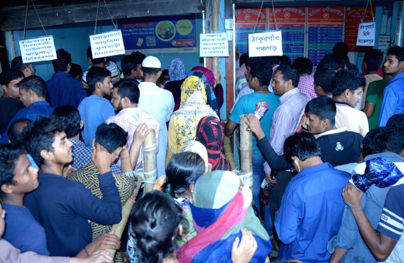 DHAKA, June 12, 2017 - People gather at the counters of a bus station to buy tickets to go home ahead of the Eid-al-Fitr festival, in Dhaka, capital of Bangladesh, on June 12, 2017.