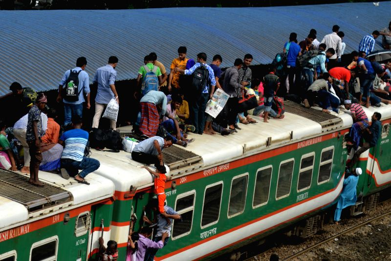 DHAKA, June 14, 2018 - People try to climb on the roof of train carriages as they head to their homes to celebrate Eid al-Fitr from Dhaka, Bangladesh, on June 14, 2018. As the Eid al-Fitr festival ...