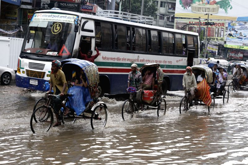 Rickshaw pullers carry passengers through the flood waters after a heavy downpour in Dhaka, Bangladesh, June 17, 2014.