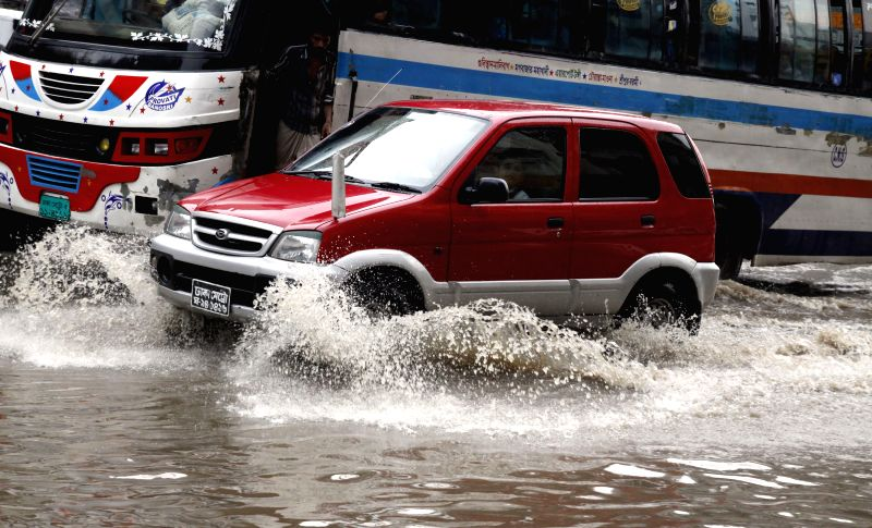 Vehicles drive through the flood waters after a heavy downpour in Dhaka, Bangladesh, June 17, 2014.