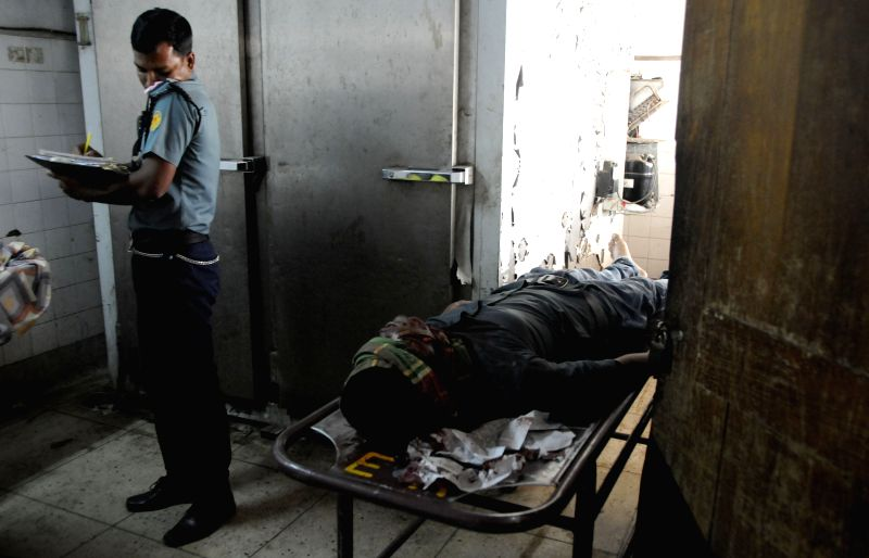 A policeman inspects the body of blogger Wshiqur Rahman, at Dhaka Medical College in Dhaka, Bangladesh, March 30, 2015. A blogger was hacked to death by ...