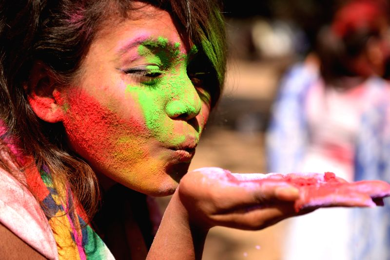 A Bangladeshi woman paints her face with colored powders to celebrate Holi festival in Dhaka, Bangladesh, March 8, 2015.