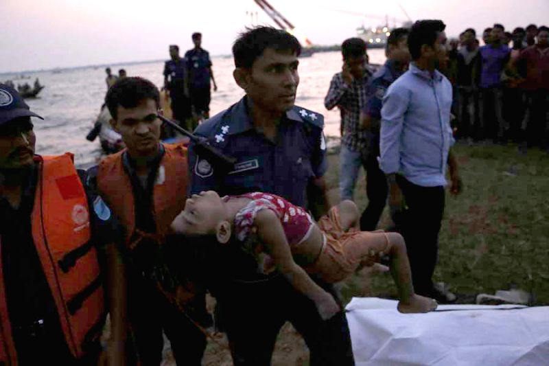 A police carries a child body after the ferry accident in Munshiganj district, Dhaka, Bangladesh, May 15, 2014. At least 12 bodies were retrieved from a ferry that ...
