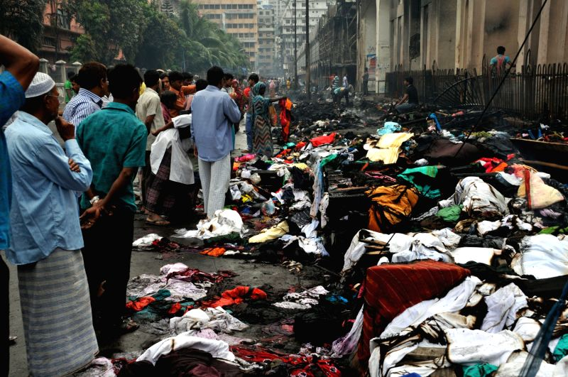 People look at products burnt by Islamist activists during a clash with police at Motijheel area in Dhaka, Bangladesh, May 6, 2013. Bangladesh police accompanied by paramilitary ..