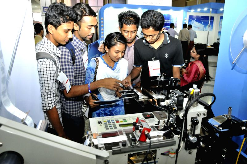 Visitors look at an equipment at a stall during the 15th Textech Bangladesh 2014 International Expo in Dhaka, Bangladesh, Sept. 3, 2014. The international exhibition .