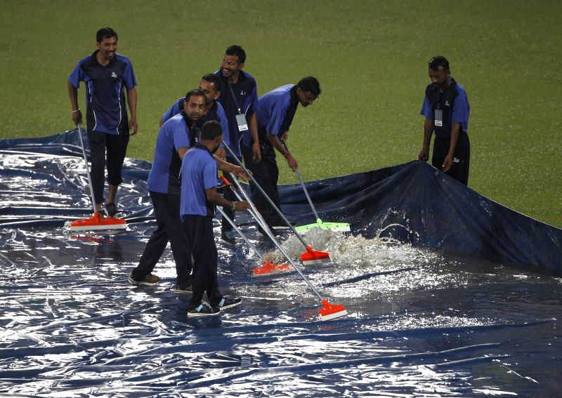 Dharamsala: Ground staff clearing water from the plastic sheets during rains ahead of the first T20I match between India and South Africa in Dharamsala on Sep 15, 2019. (Photo: Surjeet Yadav/IANS)
