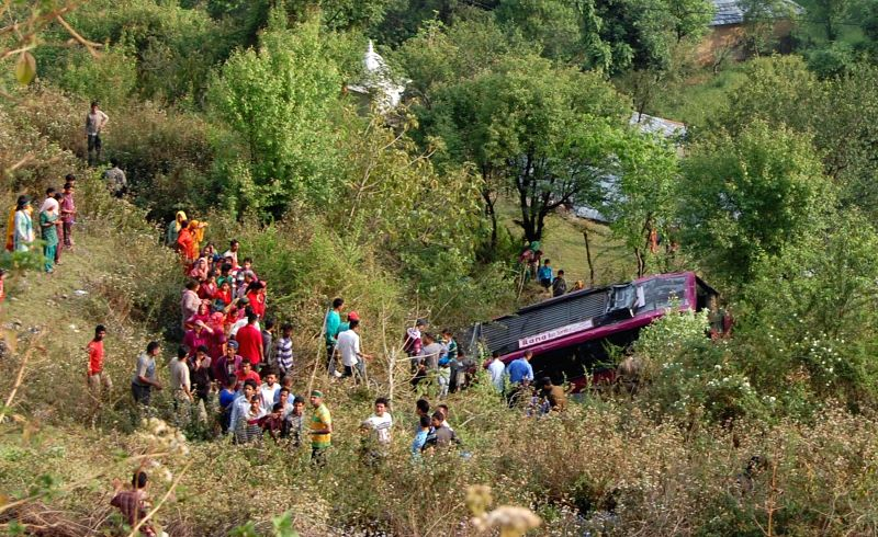 People rescue passengers of a bus that fell into a gorge near Dharamsala, Himachal Pradesh on April 13, 2015.