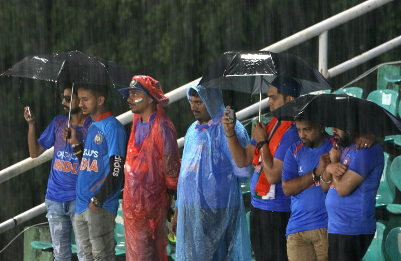 Dharamsala: Spectators shield themselves with umbrellas during rains ahead of the first T20I match between India and South Africa in Dharamsala on Sep 15, 2019. (Photo: Surjeet Yadav/IANS)