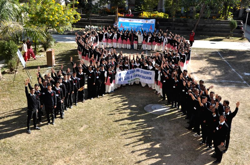 Students stand in the formation of AIDS symbol on World Aids Day in Dharamsala, on Dec 1, 2014.