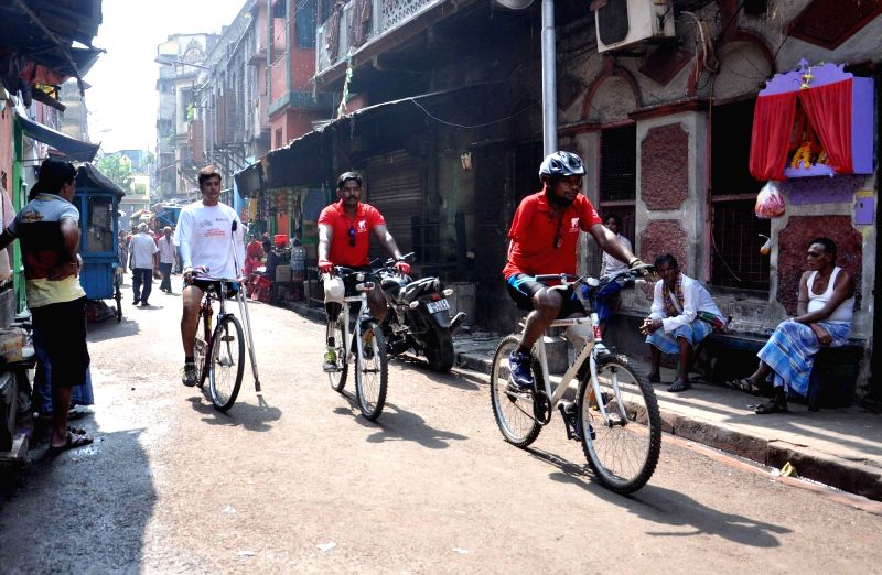 Differently abled persons with other cyclist take part in a cycle rally against AIDS/HIV campaigning from Sonagachi, way to Petrapole border in Kolkata, on Nov 15, 2015.