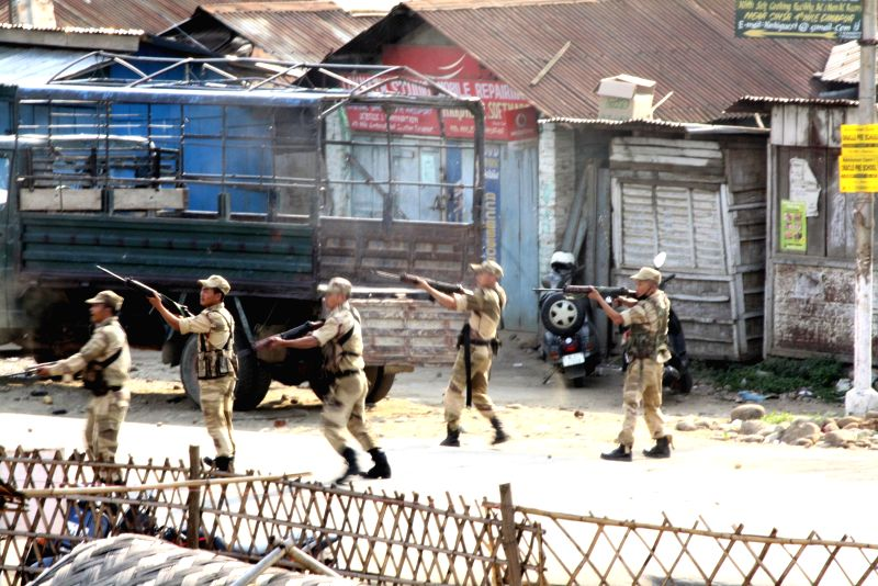 Security personnel take position as an irate mob of thousands of people storm Dimapur Central Jail on March 5, 2015. An alleged rapist, suspected to be an illegal Bangladeshi migrant, was ...