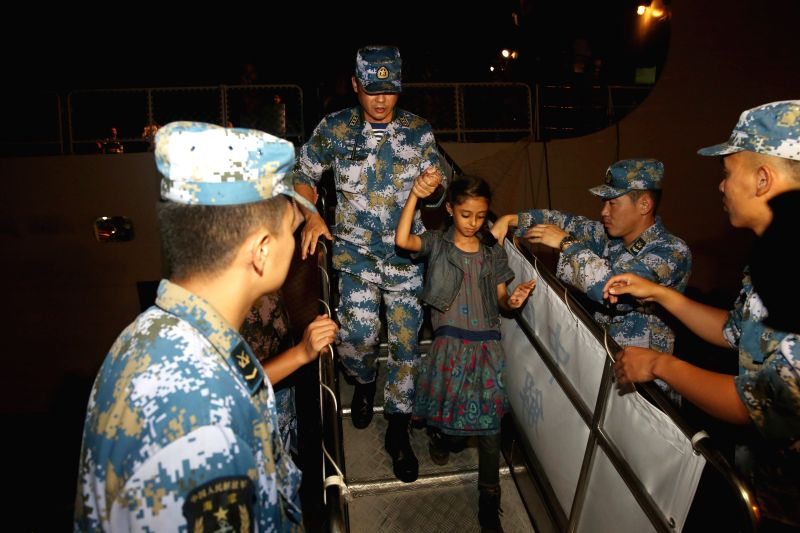 A crew member helps a girl stepping down the Chinese Linyi missile frigate in Djibouti, April 2, 2015. A total of 225 nationals from 10 countries who were ...