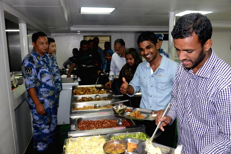 """Sri Lankan nationals queue up for meal at the Chinese """"Linyi"""" missile frigate, on April 6, 2015. A total of 38 Chinese nationals and 45 Sri Lankans ..."""