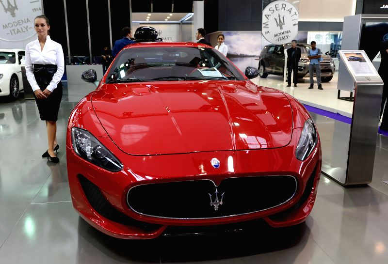 DOHA, April 19, 2017 - A model stands beside a Maserati Gran Turismo Sport during the Qatar Motor Show 2017 at the Doha Exhibition and Convention Center in Doha, Capital of Qatar, April 18, 2017. The ...