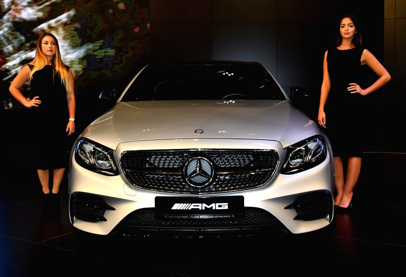 DOHA, April 19, 2017 - Models stand beside a Mercedes-AMG E43 4MATIC during the Qatar Motor Show 2017 at the Doha Exhibition and Convention Center in Doha, Capital of Qatar, April 18, 2017.The five ...