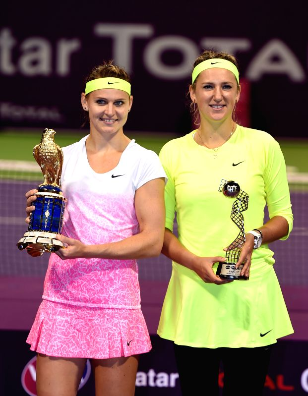Lucie Safarova (L) of the Czech Republic, the winner of the Qatar Open tennis tournament, poses next to her opponent Victoria Azarenka of Belarus following the women's ...