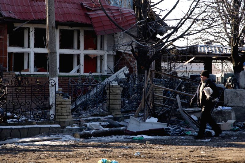 """A man walks by a destroyed building in Uglegorsk, Ukraine, on Feb, 21, 2015. UN Secretary-General Ban Ki- moon said on Friday that the UN would """"stand guided ..."""