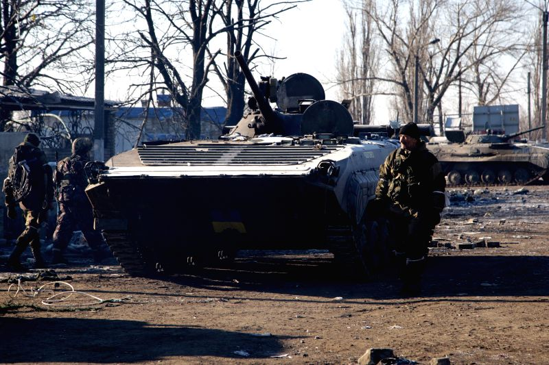Local militia fighters walk next to a sezied Ukrainian NPS in Uglegorsk, Ukraine, on Feb, 21, 2015. UN Secretary-General Ban Ki- moon said on Friday that the UN ...