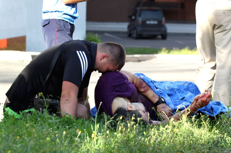 A man mourns his friend, a policeman killed during an assault in eastern Ukrainian city of Donetsk, July 1, 2014. A group of unknown armed people stormed the ...
