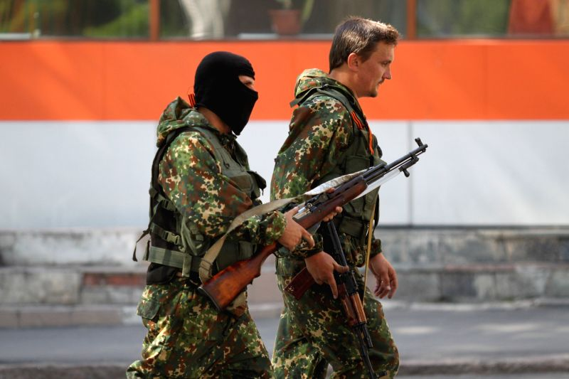 An armed man of local militia walk in the street near the place of an assault in eastern Ukrainian city of Donetsk, July 1, 2014. A group of unknown armed people ...
