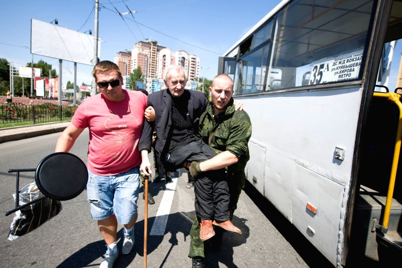 Local residents get on the bus to fleet the battle zone in Donetsk, east Ukraine, July 21, 2014. At least three people were killed as heavy fighting erupted in the .