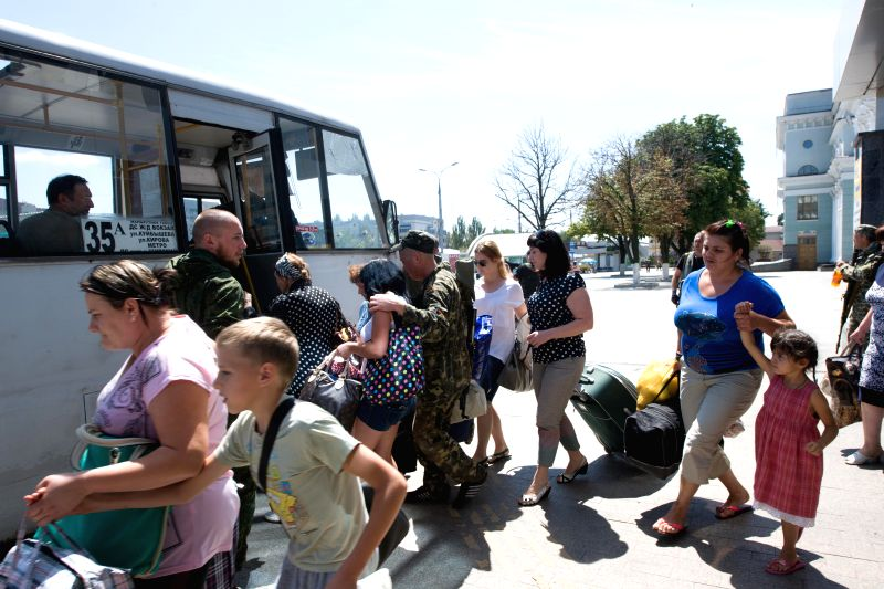 Local residents just arrived at the train station get on the bus to fleet the battle zone in Donetsk, east Ukraine, July 21, 2014. At least three people were killed