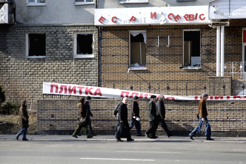 People pass by damaged buildings in a district close to airport, in Donetsk, Ukraine, on March 21, 2015.