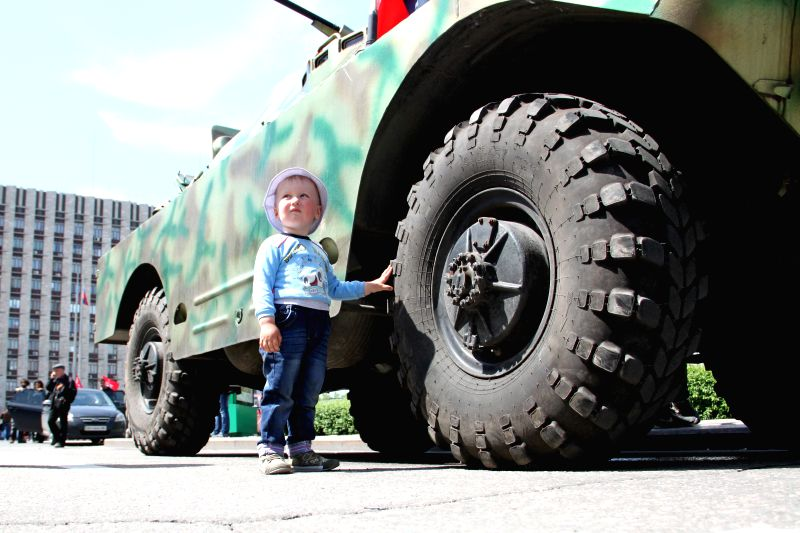 A boy stands by an armored vehichle in Donetsk, Ukraine, May 10, 2014. A referendum in eastern Ukraine's Donetsk region will go ahead as scheduled on Sunday, local ..
