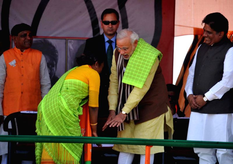 A woman tries to touch the feet of Prime Minister Narendra Modi during a rally in Dumka of Jharkhand  on Dec 15, 2014. - Narendra Modi