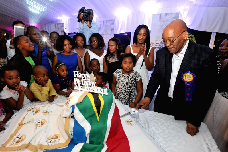 South Africa's President Jacob Zuma (1st R) tries to cut the birthday cake with his family members during a private family gathering at the presidential official ...