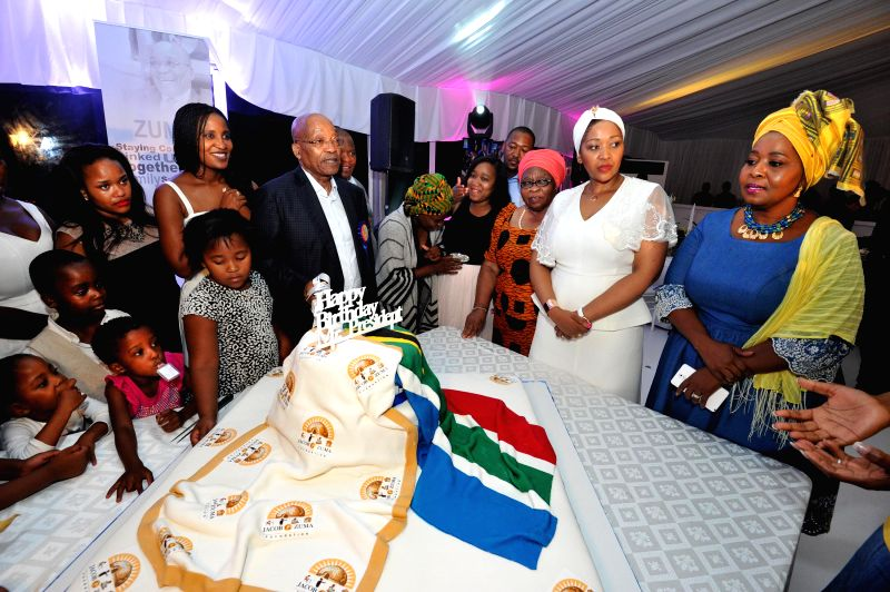 South Africa's President Jacob Zuma (C) tries to cut the birthday cake with his family members during a private family gathering at the presidential official ...