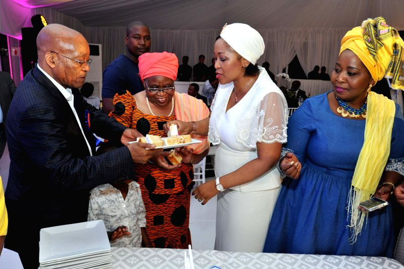 South Africa's President Jacob Zuma (1st L) shares pieces of his birthday cake with his wives Sizakele Zuma (2nd L), Tobeka Zuma (2nd R) and Bongi Zuma (1st R) ...