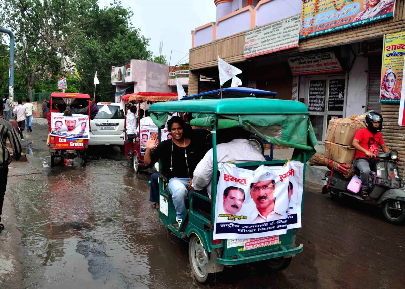 E-rickshaws with posters of Aam Aadmi Party (AAP) leader Arvind Kejriwal behind them participate in a road show at Bhajanpura in North East Delhi on July 2, 2014. - Arvind Kejriwal