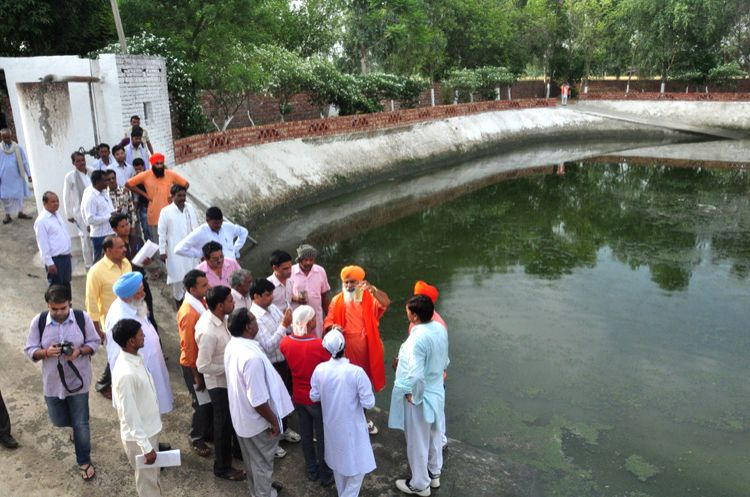 Eco warrior Balbir Singh Seechewal (in red robes) explains how to treat village sewage and reuse it safely for irrigating fields. His low-cost community managed treatment techniques have been ... - Balbir Singh Seechewal
