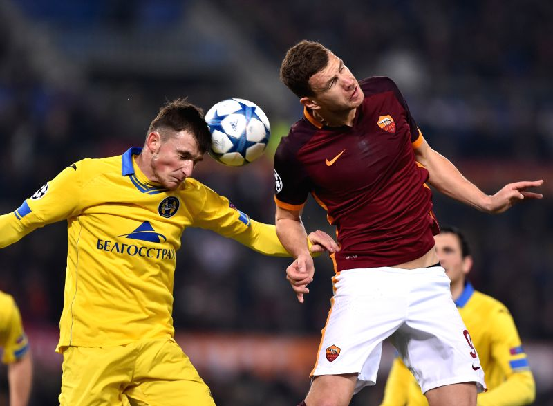 Edin Dzeko (R) of Roma fights for the ball with Evgeni Yablonski of Bate Borisov during the UEFA Champion's League football in Rome, Italy, Dec. 10, 2015. Roma won ...