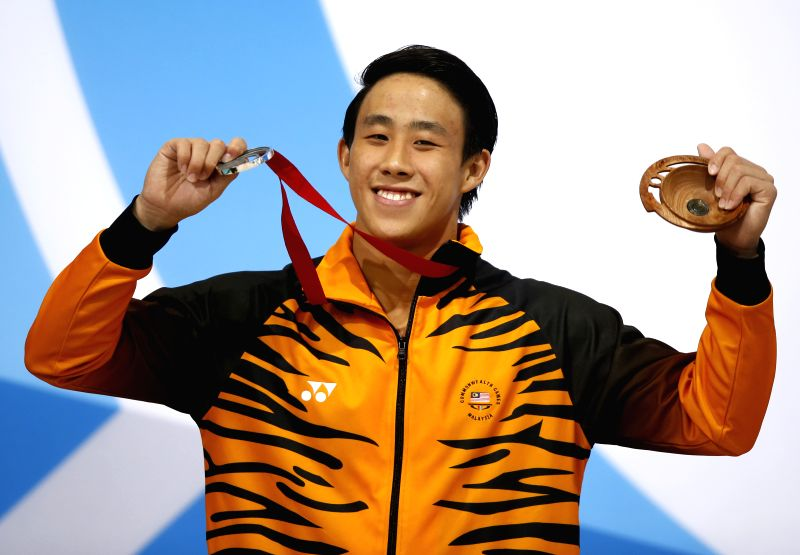 Silver medalist Ooi Tze Liang of Malaysia celebrates on the podium during the medal ceremony for the Men's 10M Platform Final of diving on day 10 of the Glasgow ...