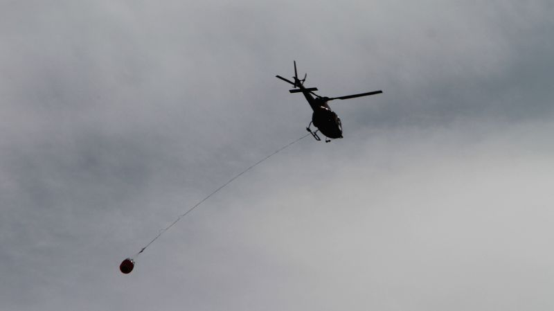 EDMONTON, May 8, 2016 - A helicopter flies overhead with a bucket of water near the wildfire site in Alberta Province of Canada, May 7, 2016. The massive wildfire in Alberta Province has covered more ...