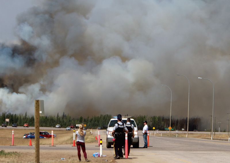 EDMONTON, May 8, 2016 - Policemen gather near the wildfire site in Alberta Province of Canada, May 7, 2016. The massive wildfire in Alberta Province has covered more than 2,000 square kilometers by ...