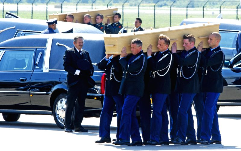 People carry a coffin containing the remains of a victim of crashed Malaysia Airlines flight MH17 during a ceremony at Eindhoven airport in the Netherlands, on ...
