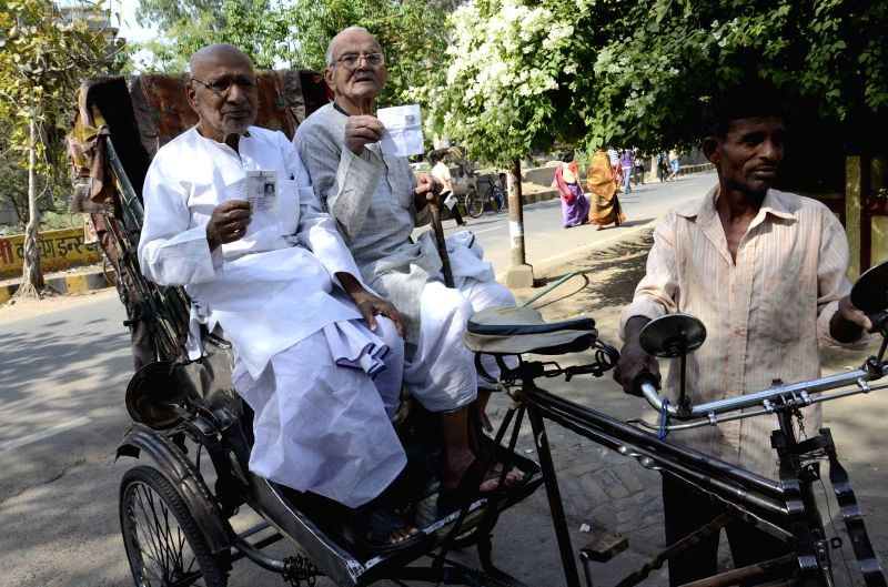 Elderly people hold their voters' identity card as they arrive to cast their votes during the fifth phase of Lok Sabha Polls in Patna on April 17, 2014.