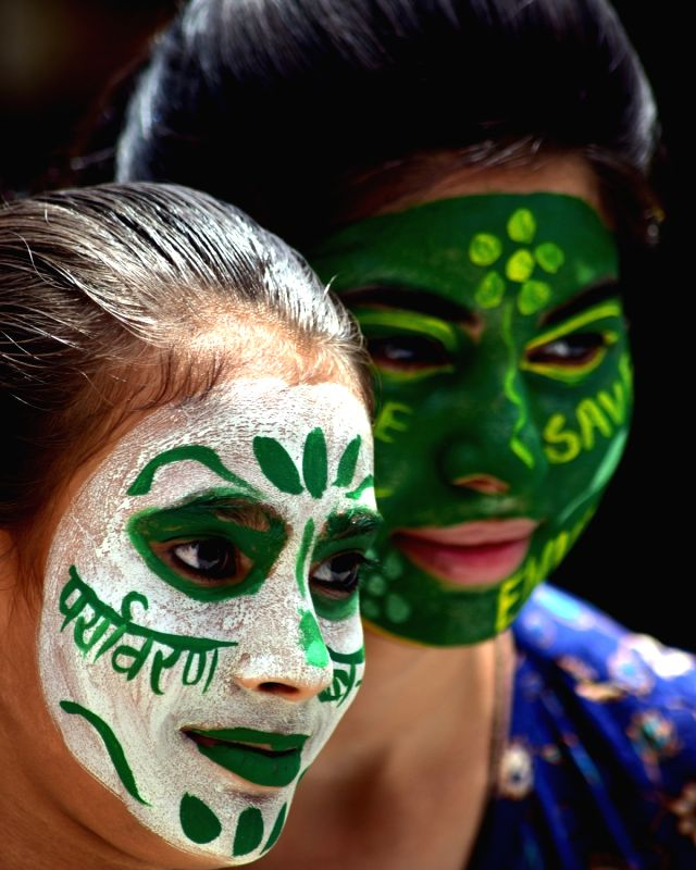 Environment activists paint their faces on the eve of World Environment Day in Bikaner on June 4, 2017.