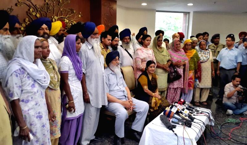 External Affairs Minister Sushma Swaraj and Punjab Chief Minister Parkash Singh Badal with family members of Indians who are trapped in violence-hit Iraq during a press conference in New Delhi on ... - Parkash Singh Badal