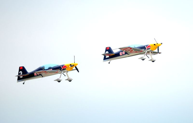 Two planes of the Red Bull Aerobatic Team fly in formation in a training in Faku, northeast China's Liaoning Province, Aug. 25, 2014. The Red Bull Aerobatic Team of ...