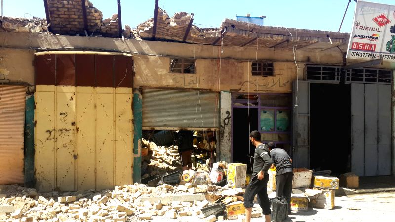 People stand by a damaged shop after an Iraqi Air Force bombing in Islamic State (IS) militants-seized city of Fallujah, some 50 km west of Baghdad, Iraq, April 2, ...