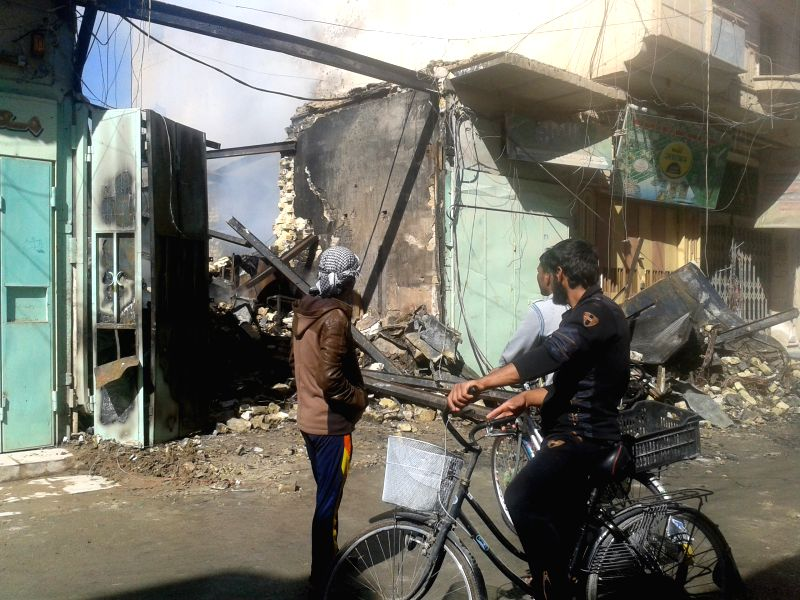 Civilians look at a damaged house after Iraqi Air Force's bombing in Islamic State (IS) militants-seized city of Fallujah, some 50km west of Baghdad, Iraq, March ...